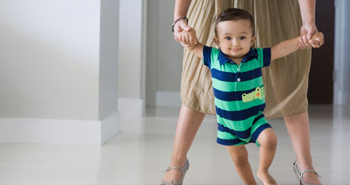 Child taking first steps with parent guardian